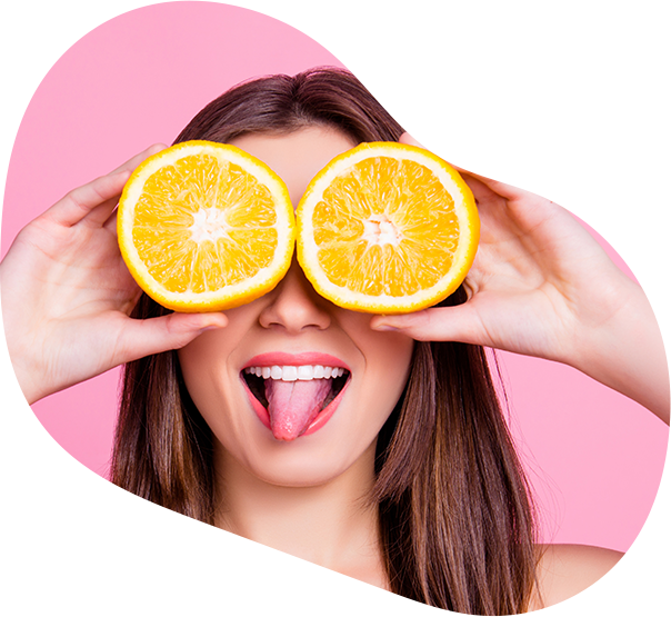 Playful woman holding oranges over her eyes and making a silly face.